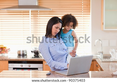 Young mother and daughter using laptop in the kitchen together