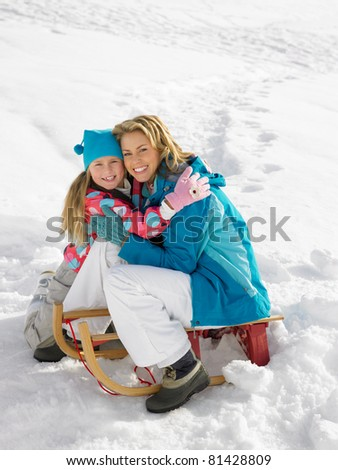Young Mother And Daughter With A Sled In The Snow