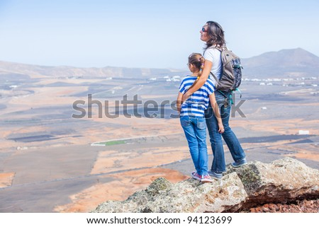 Young mother and daughter with backpack standing on cliff's edge and looking to a sky - stock photo