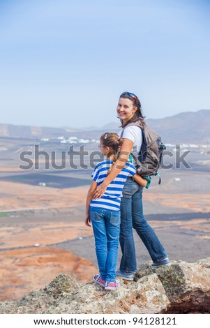Young mother and daughter with backpack standing on cliff's edge and looking to a sky. Vertical view - stock photo