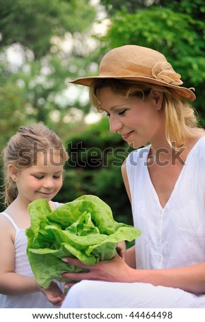 Young mother and daughter with lettuce