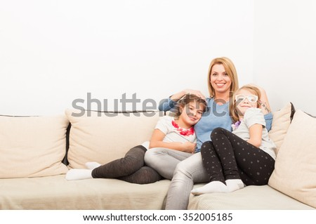 Young mother and daughters  bonding on at home on a couch or sofa - stock photo