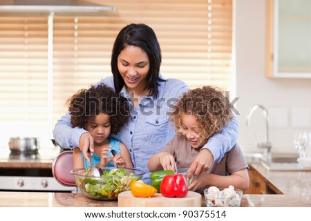 Young mother and daughters preparing salad in the kitchen together - stock photo