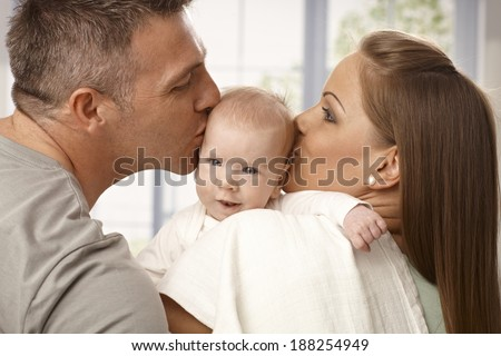 Young mother and father holding newborn baby, kissing head from two sides. - stock photo
