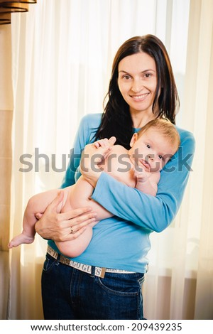 Young mother and her adorable baby boy. Beautiful mother holding baby boy, mom carry cute child adorable small son, happy family picture, mom and kid indoor brunette Arabic models, happiness concept - stock photo