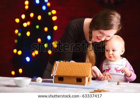 Young mother and her adorable baby daughter decorating gingerbread house - stock photo