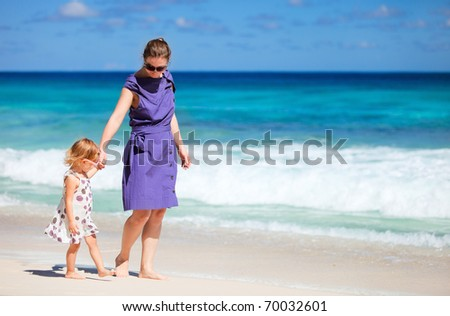 Young mother and her adorable daughter enjoying day at beach - stock photo
