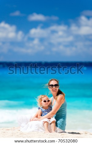 Young mother and her adorable daughter enjoying day at beach