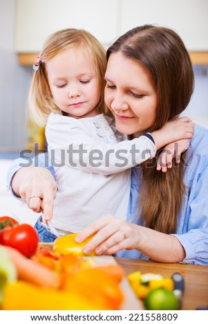 Young mother and her adorable little daughter cooking together at home - stock photo