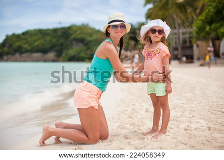 Young mother and her adorable little daughter have fun at tropical beach - stock photo