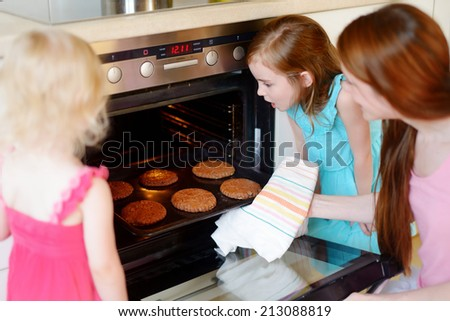 Young mother and her adorable little daughters baking cookies at home in a kitchen - stock photo