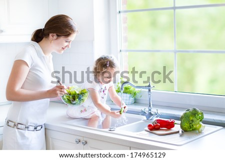 Young mother and her adorable toddler daughter cooking salad together in a beautiful white kitchen with a big garden view window - stock photo