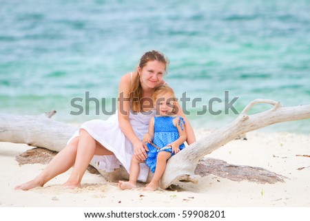 Young mother and her adorable toddler daughter sitting on exotic beach