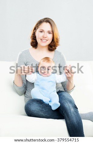 Young mother and her baby child. Infant son and his mum. - stock photo