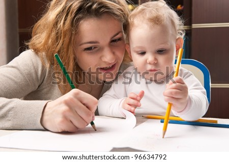Young mother and her baby daughter drawing with pencils - stock photo