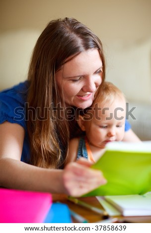 Young mother and her baby daughter reading together. Can be used also in kindergarten/daycare context. - stock photo