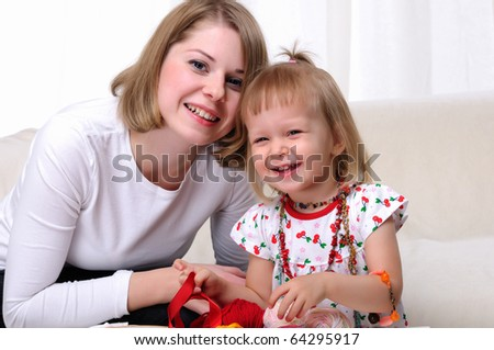 Young mother and her baby daughter spending time together. Dress up in costume jewelry. - stock photo