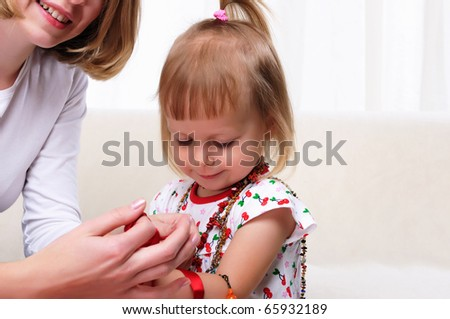 Young mother and her baby daughter spending time together. Dress up in costume jewelry.