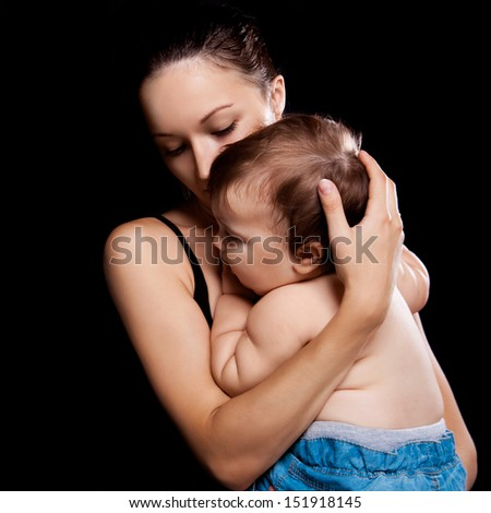young mother and her baby in the studio, isolated on black background (focus on the baby) - stock photo