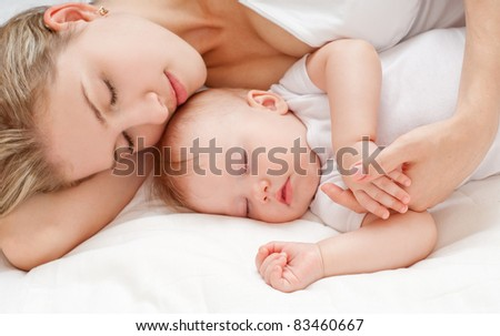 Young mother and her baby, sleeping in bed - stock photo