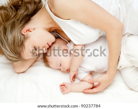 Young mother and her baby, sleeping in bed