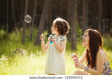 Young mother and her child playing with soap bubbles - stock photo