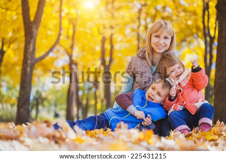 Young mother and her children have fun in the autumn park - stock photo