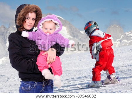 Young mother and her childs spent free time together on the snow. - stock photo