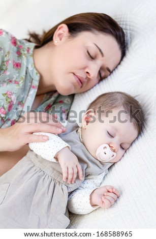 Young mother and her cute baby girl sleeping together in the bed
