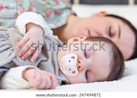 Young mother and her cute baby girl sleeping together in the bed - stock photo