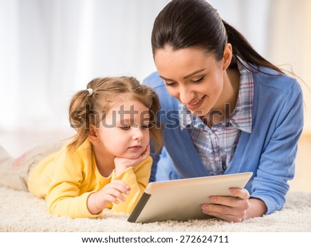 Young mother and her cute daughter are looking at laptop. - stock photo