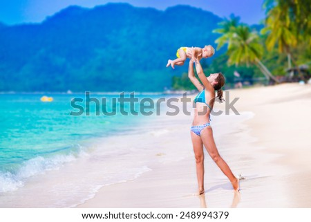 Young mother and her cute little baby running and playing on a beautiful tropical beach enjoying family summer holiday - stock photo