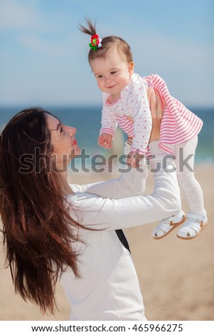 Young mother and her cute little daughter playing and smiling on the beach of sea