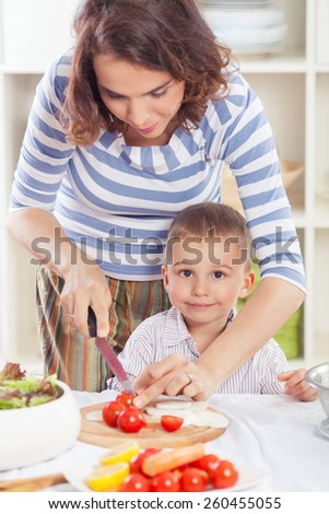 Young mother and her cute little son preparing meal in the kitchen  - stock photo