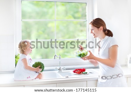 Young mother and her cute toddler daughter cooking together a healthy salad for lunch in a beautiful  white sunny kitchen with a big window  - stock photo