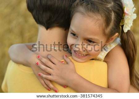 Young mother and her daughter at the wheat field - stock photo