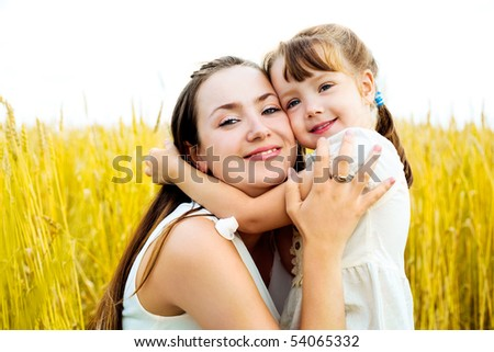 young mother and her daughter at the wheat field on a sunny day - stock photo
