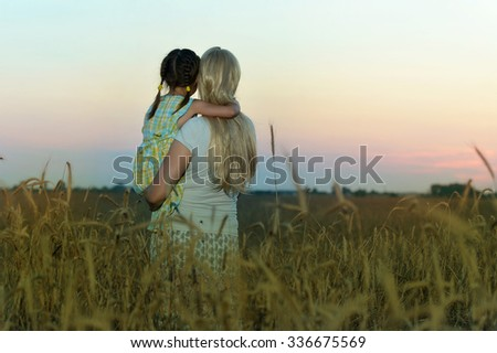 Young mother and her daughter at the wheat field on sunset,woman pointing at something,back view - stock photo