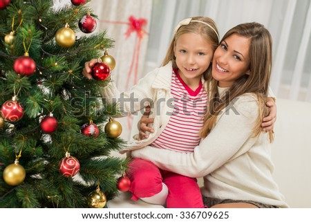 Young mother and her daughter decorating Christmas tree at home.  - stock photo