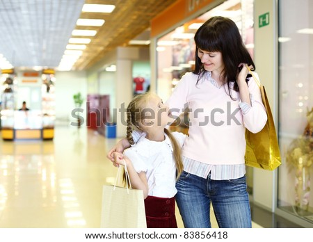Young mother and her daughter doing shopping together - stock photo