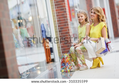 Young mother and her daughter doing shopping together. Woman with child on shopping in shopping mall with bags. Woman with child having fun and enjoying shopping time - stock photo