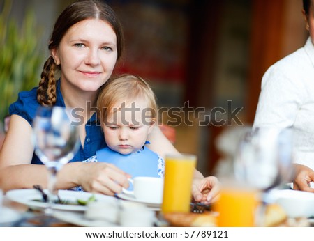 Young  mother and her daughter having breakfast together