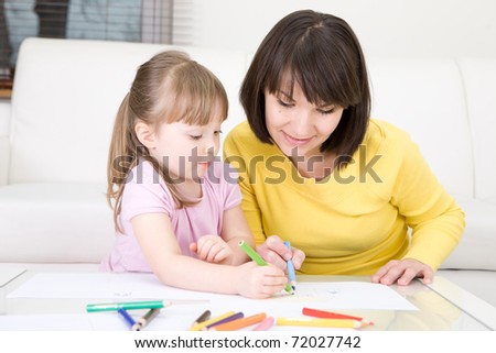 young mother and her daughter having fun in kindergarden - stock photo