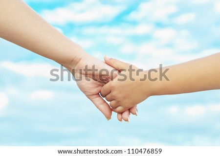 Young mother and her daughter holding hands - stock photo