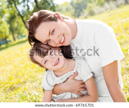 young mother and her daughter in the park on a sunny autumn day - stock photo