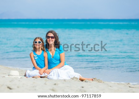 Young mother and her daughter on tropical white sand beach