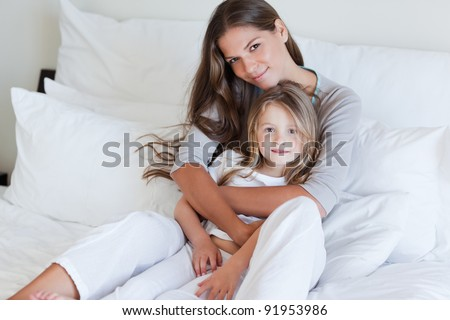 Young mother and her daughter posing on a bed while looking at the camera - stock photo