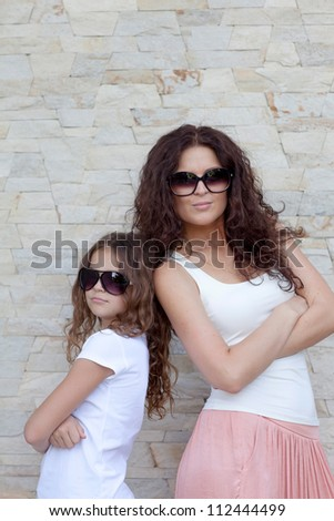 Young mother and her daughter standing back to back and smiling - stock photo
