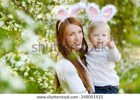 Young mother and her daughter wearing bunny ears in a spring garden on Easter day - stock photo
