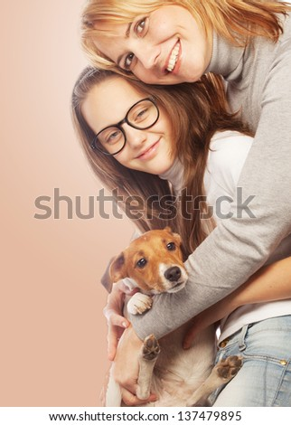 Young mother and her daughter with Jack Russell Terrier. - stock photo